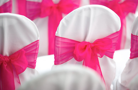 white chair covers fucshia sashes